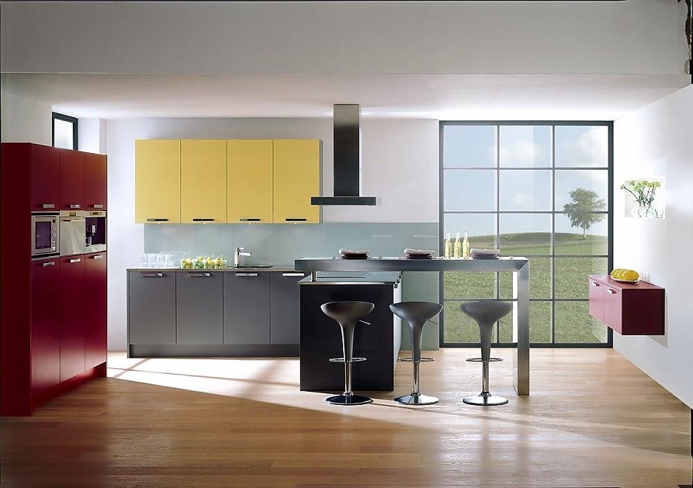 Cocina en L de colores con los armarios en gris, burdeos y amarillo.