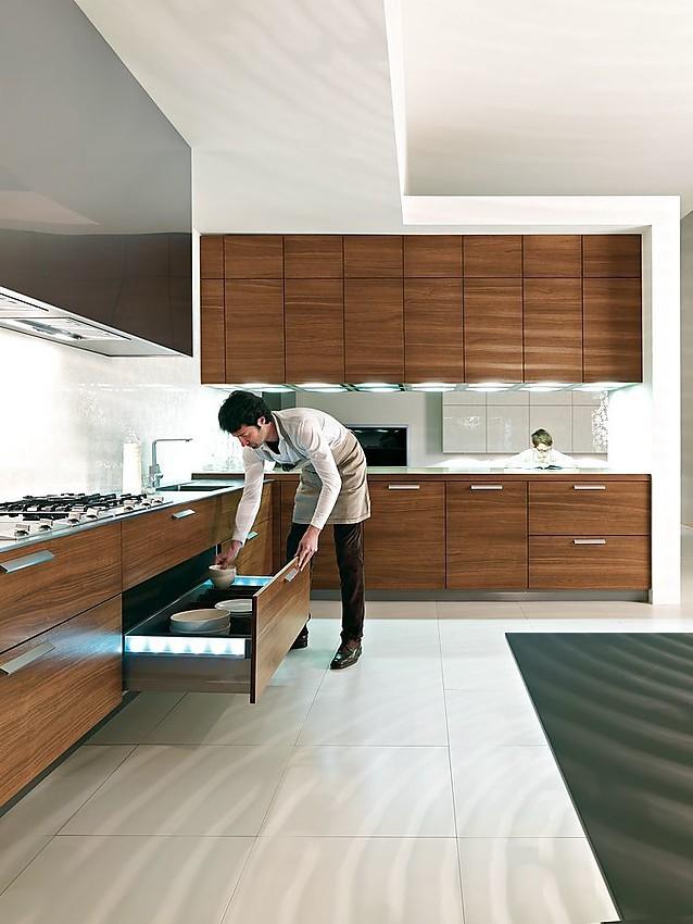 Cocina en L de nogal, acero y blanco con elementos de iluminación